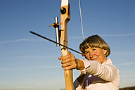 Senior adult woman using bow and arrow - WESTF03467
