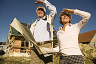 Senior couple holding plan in front of partially built house - WESTF03455