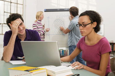 Young couple standing by flipchart, focus on man and woman using laptop in foreground - WESTF03627