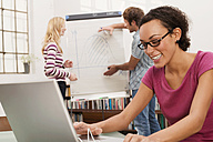 Young man explaining woman chart in background, focus on woman using laptop, smiling - WESTF03624