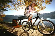 Woman biking at lake with child in trailer - MRF00799