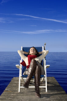 Young woman sitting in deck chair on jetty, eyes closed - LDF00402