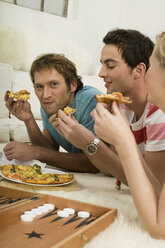 Three young people lying on floor, eating pizza - WESTF03701