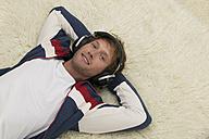 Young man lying on floor, wearing headphones, elevated view - WESTF03683