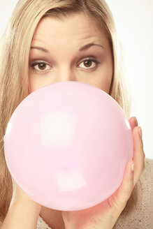 Young woman blowing up balloon - LDF00446