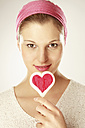 Young woman holding heart shaped lollipop, close-up, portrait - LDF00443
