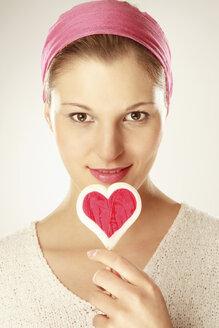 Young woman holding heart shaped lollipop, close-up, portrait - LDF00443