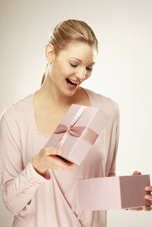 Young woman holding gift box, close-up - LDF00419