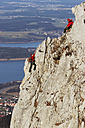 Germany, Bavaria, two people climbing on rock face - FFF00744