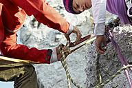 Germany, Bavaria, young couple preparing climbing rope - FFF00732