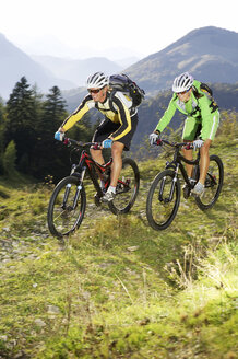 Austria, Tirol, young couple riding bicycles on mountain - FFF00712