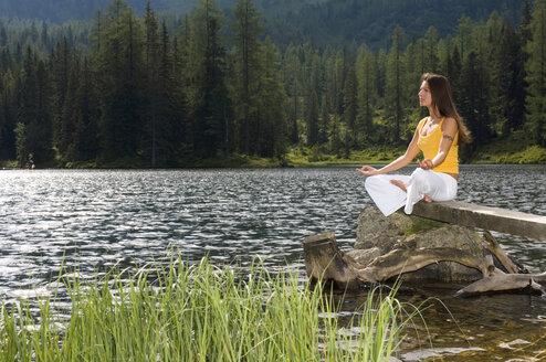 Woman exercising yoga at lake, side view - HHF01145
