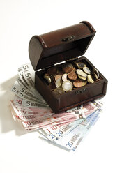 Open cash, full of coins, standing on bank notes, elevated view - 05941CS-U