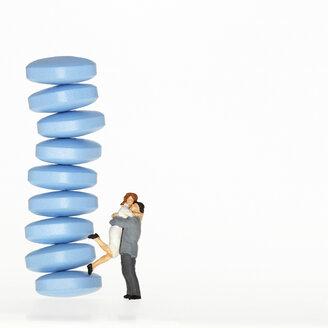Man embracing woman next to pile of  pills - CHKF00263