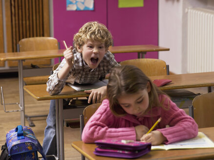 Boy (4-7) shouting behind girl in class room - WESTF04596