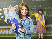 Girl (6-7) holding school cone, smiling, portrait - WESTF04495