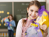 Girl (6-7) holding school cone, smiling, portrait, close-up - WESTF04465