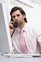 Businessman sitting by computer, using landline phone, close-up - WESTF04848