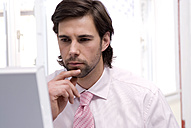 Businessman using computer, hand on chin, close-up - WESTF04845