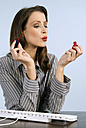 Businesswoman applying nail polish, blowing, close-up - WESTF04824