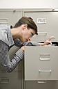 Businesswoman looking through filing cabinet, close-up - WESTF04763