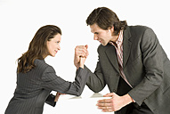 Businessman and businesswoman arm-wrestling, side view - WESTF04689