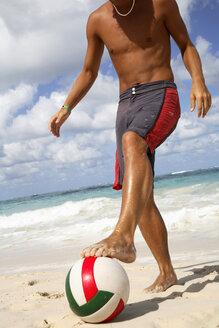 Young man playing football on beach - PKF00023