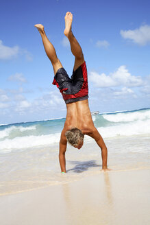 Young man making handstand on beach - PKF00007