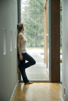 Woman in a hall looking out of window - NHF00445