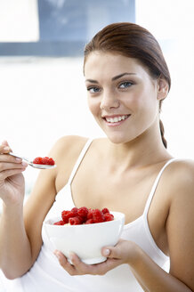 Young woman holding bowl with rasberries - WESTF05050
