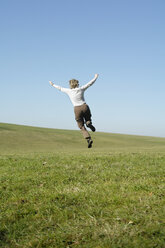 Woman jumping in meadow, rear view - GNF00915