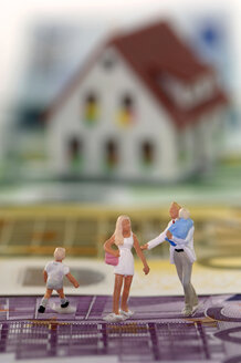 Pastic figurines on banknotes, house in background - ASF03155