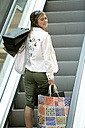 Young woman carrying shopping bags, rear view - KMF01002