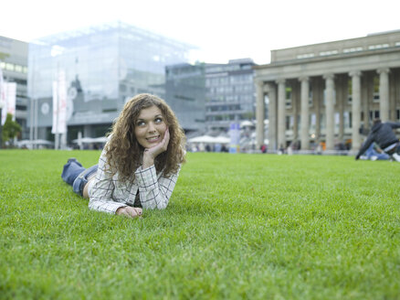 Germany, Stuttgart, young woman lying in meadow - KMF00973