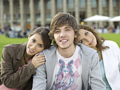 Germany, Stuttgart, young people sitting on bench - KMF00964