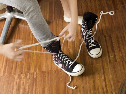 Young woman binding shoes, detail - KMF00940