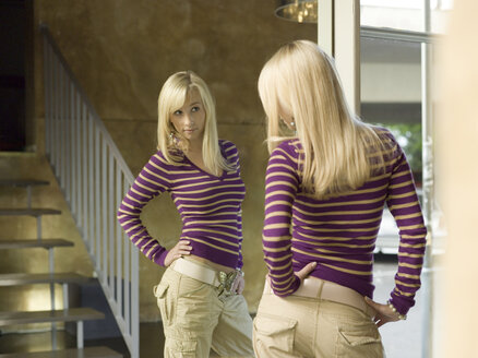 Young woman viewing herself in mirror - KMF00871