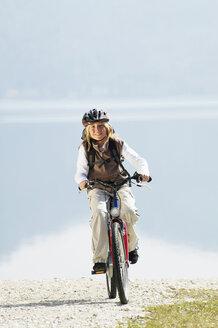 Germany, Bavaria, Walchensee, girl riding a bike - MRF00894