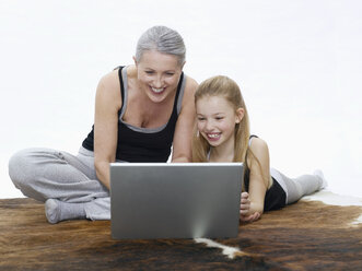 Grandmother and granddaughter using laptop, portrait - WESTF05375