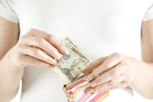 Woman putting Dollar notes in change purse, close-up - CLF00351