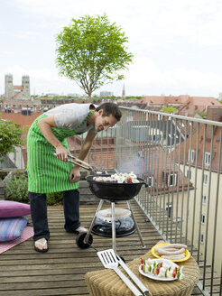 Man preparing barbecue on balcony - WESTF05919
