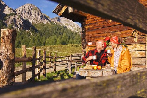 Couple sitting in front of alpine hut - HHF01492