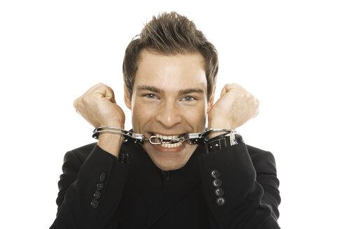 Young man wearing handcuffs, close-up - PKF00176