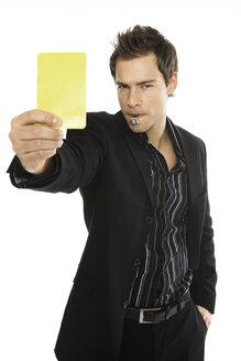 Young man showing yellow card, close-up - PKF00167