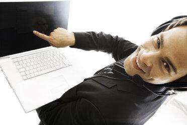 Young man wearing head set, holding laptop, close-up - PKF00140