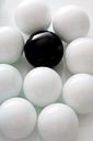 Black ball between several white balls, close-up - MAEF00434