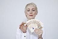 Young woman holding money, portrait - TCF00185