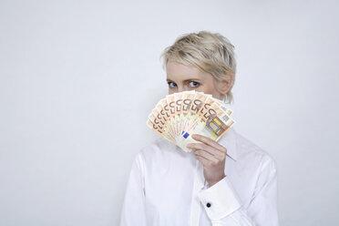 Young woman holding money, portrait - TCF00179