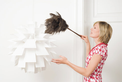 Woman dusting a lamp with a feather duster - NH00663