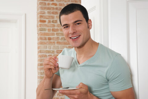 Young man holding a cup of coffee, portrait, close-up - NH00627